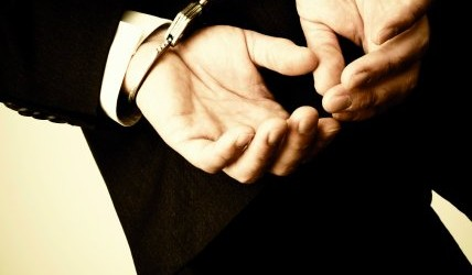 Businessman hand cuffed, close-up toned image